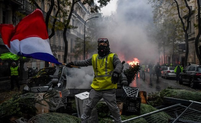 A demonstrator holds a French flag during a protest of Yellow vests