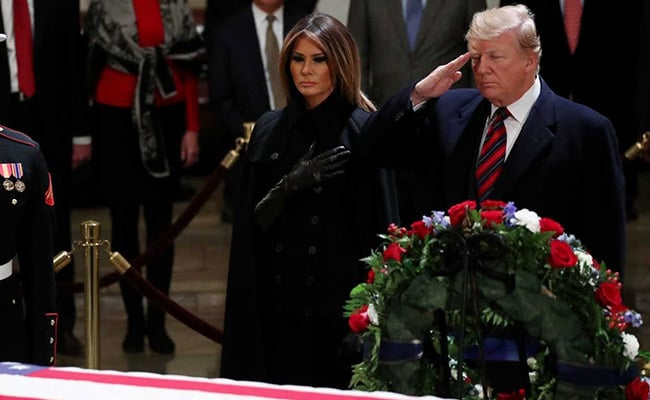 Bob Dole stands to salute George H. W. Bush at capitol memorial