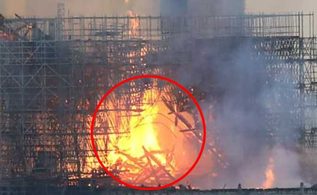 Is there a man seen standing on the scaffolding above the fire? Enahmsrc_notre-dame-fire-jesus-christ_625x300_18_April_19