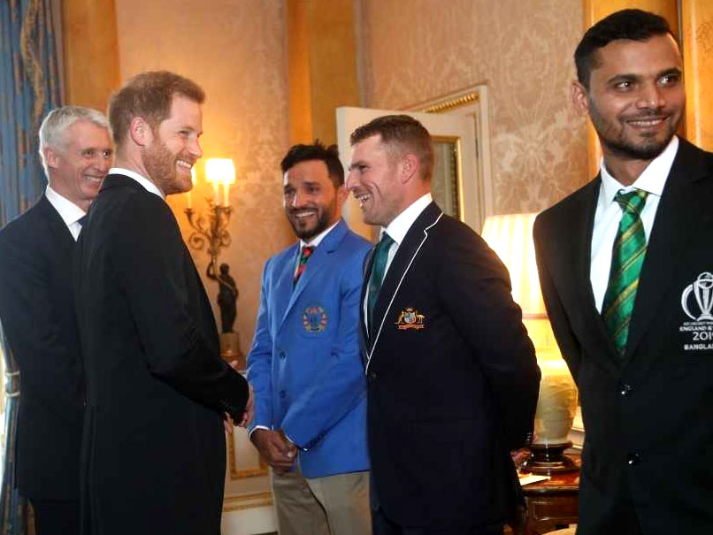 Prince Harry takes a copy of Aaron Finch during the Buckingham Palace Party