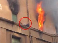 In Dramatic Video, Man Clings To Building Ledge As Flames Rage Inside