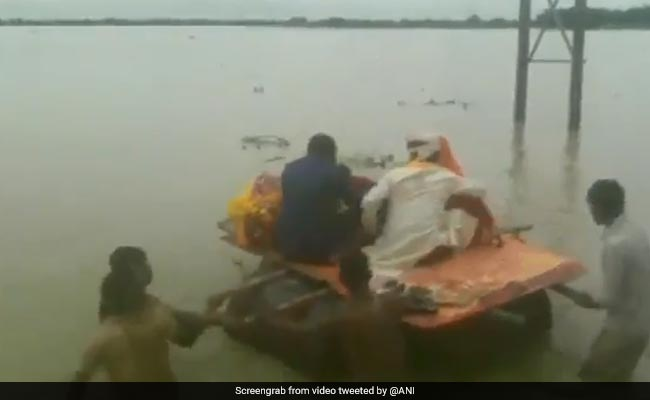 On Video, Newly Married Couple Cross Flooded Road Using Makeshift Boat