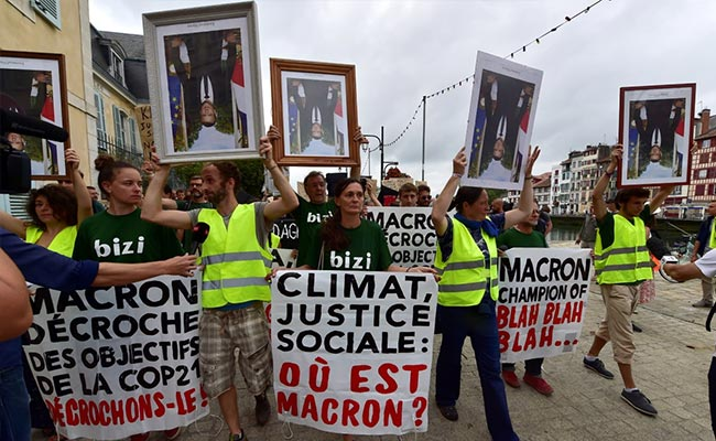 Anti-G7 Protesters March With 'Stolen' Portraits Of Emmanuel Macron