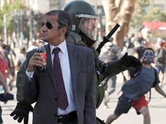 In Dark Glasses, Smartly-Dressed Chilean Sips Soda As Riot Rages Around