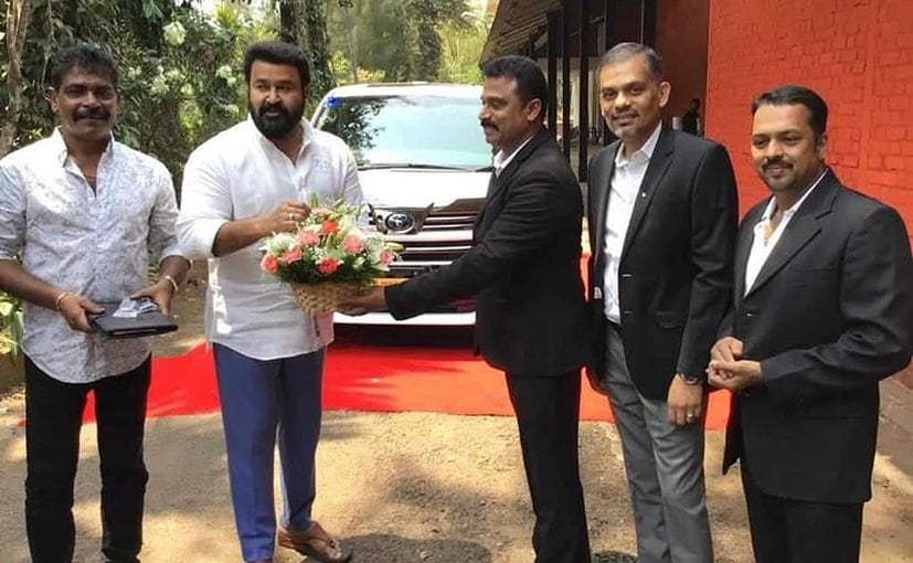 Actor Mohanlal accepts delivery of his new Toyota Vellfire from dealership representatives