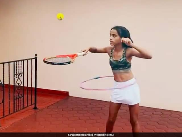 Young Girl Shows Off Tennis Skills While Doing Hula Hoops. Watch