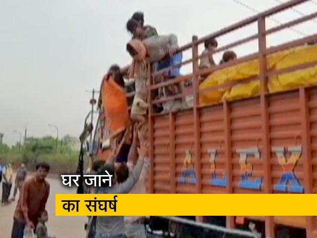Videos : एक हाथ में बच्चे को लेकर दूसरे हाथ से ट्रक में चढ़ने की कोशिश करता नजर आया मजदूर
