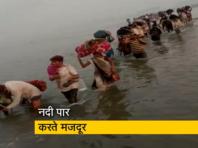 Migrant laborers on their way home through the river - नदी से ...