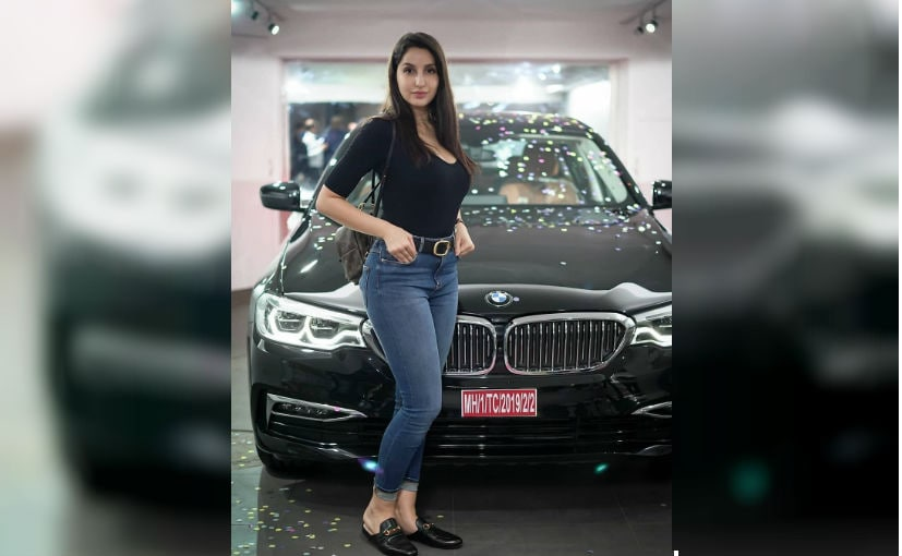 Actor Nora Fatehi poses with her new BMW 5 Series. The images were shared by BMW India