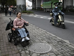 Wheelchair Users In China Dodge Traffic On Rough Road To Recognition