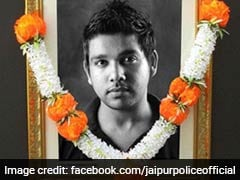 The young man in a garlanded photograph of a