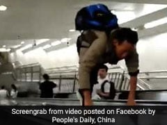 Man Climbs Up On Section Between Two Escalators. Onlookers Watch In Shock