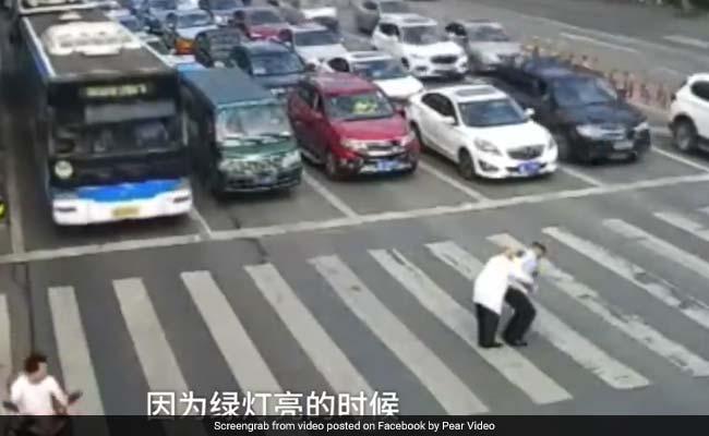 Watch: Cop Carries Elderly Man Across Road In Viral Video