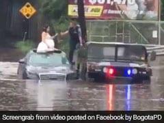 बाढ़ में फंसी दुल्हन, जान बचाने के लिए दूल्हे को छोड़ बैठ गई कार के ऊपर, देखें VIDEO