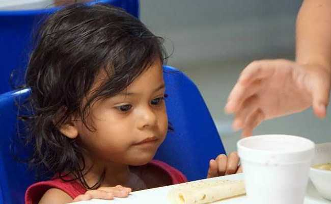 A young girl being served a cup of soup by volunteers in a migration center in the border town of McAllen Texas