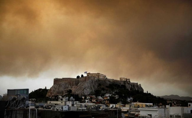 Scores dead as wildfires tear through tourist resorts near Greek capital